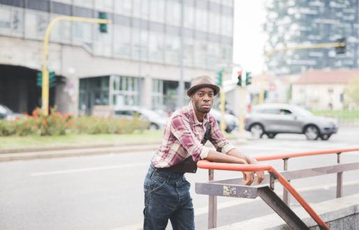 man leaning against a hand rail near a street, thinking deeply about something