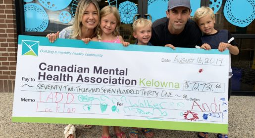 family of 5 is holding a large check payable to CMHA Kelowna for $72000 the family looks very happy and the 3 kids can barely hold up the massive check