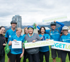 Eight people with bicycle helmets and CMHA Blue shirts holding signs for # Get Loud fundraisers