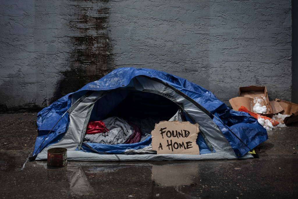 """a tent sitting open on a street where someone who was previously homeless used to live. the open fly of the tent reveals a carboard sign that reads """"found a home"""""""