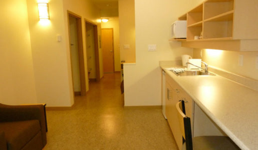 Interior picture of one of CMHA Kelowna's many supportive housing units. A clean kitchen and living room as well as a room and a bathroom. Well lit and furnished