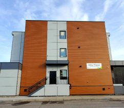 CMHA's newest supportive housing unit, a brown and grey modern looking modular building on a cloudy day