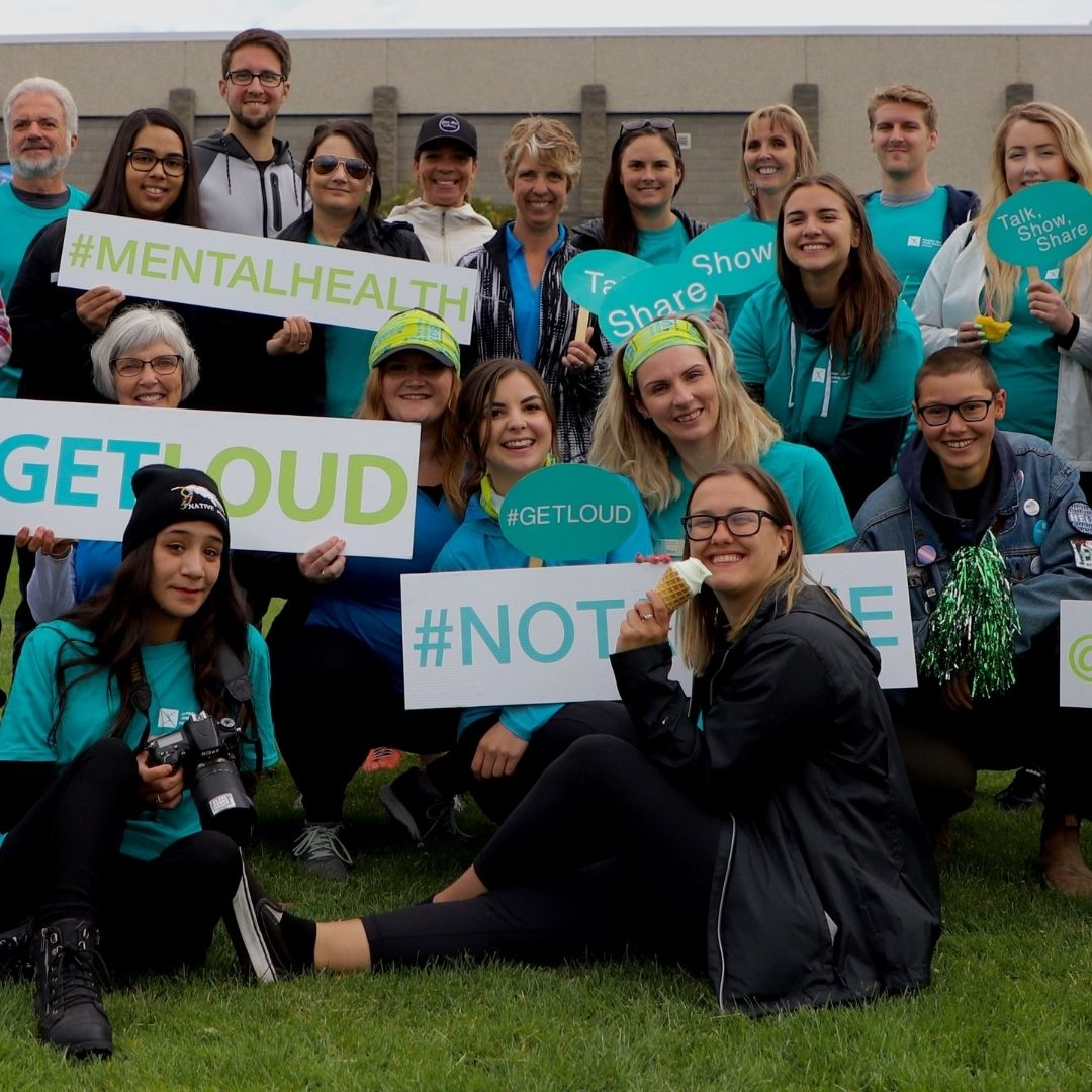 Group volunteer photo for # Get Loud for mental health everyone wearing CMHA blue get loud shirts and lots of signs for mental health