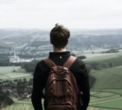 Teenager staring out over a foggy valley wearing a backpack