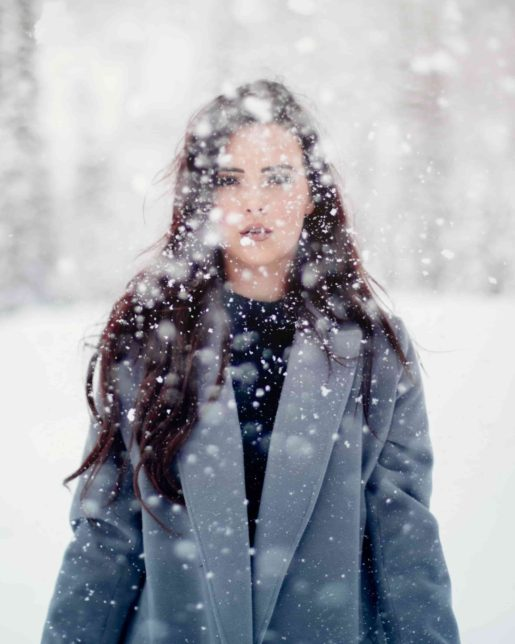 woman with long hair and a winter coat standing outside as it snows heavily
