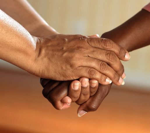 Holding a hand supportively in both hands